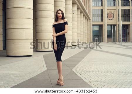 Young elegant girl posing at city street. Pretty beautiful business woman in elegant black dress against city background. Full length horizontal portrait. - stock photo