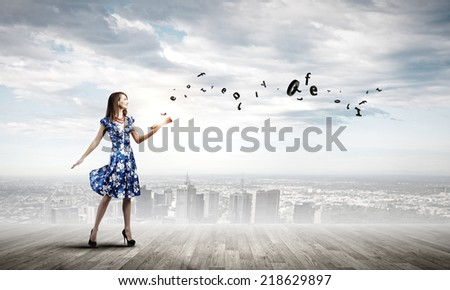 Young elegant lady in blue dress with book in hand - stock photo