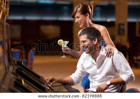 young elegant lady standing, boyfriend playing slot machine - stock photo