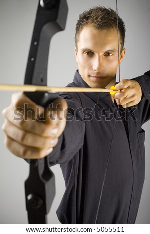 Young, elegant man in black shirt holding bow and shooting to target. Gray background, front view - stock photo