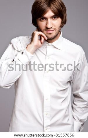 young elegant man in white shirt, studio shot - stock photo