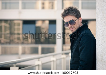 Young elegant man portrait with glasses with building background. - stock photo