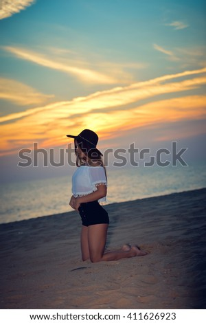 Young elegant pretty lady with a hat on the beach dawn outdoors background, portrait. Romantic view - stock photo
