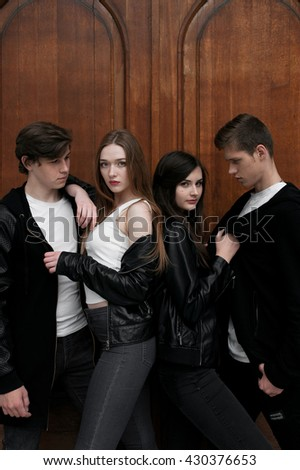 Young elegant trendy friends outdoors, wearing black and white clothing, retouched shot - stock photo