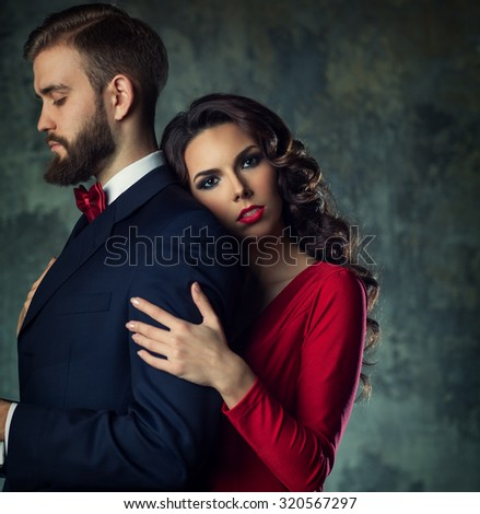 Young elegant woman embracing man. He is serious and looking aside. Quarrel concept. - stock photo