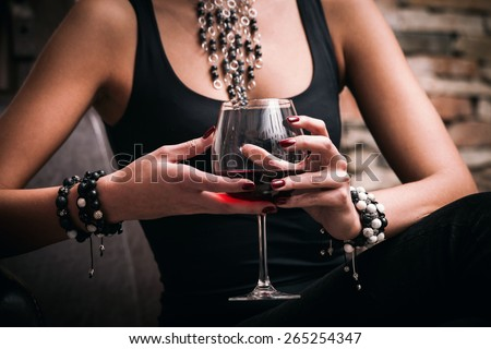 young elegant woman hold glass of red wine, indoor shot, selective focus - stock photo