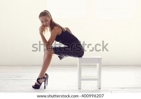 Young elegant woman in a black dress posing on a chair in a white studio. - stock photo