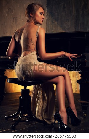 Young elegant woman in dress playing piano in retro style interior. Tattoo on woman back. - stock photo