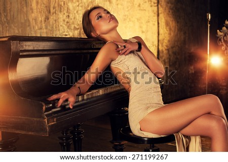 Young elegant woman in dress sitting at piano in retro style interior. - stock photo