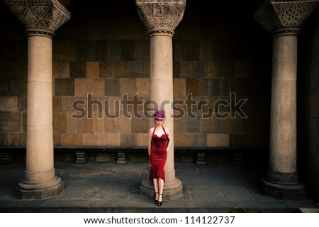 young elegant woman in red dress and cylinder   against column, full body shot - stock photo