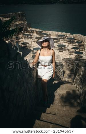 Young elegant woman wearing hat walking up stone stairways at seaside castle - stock photo