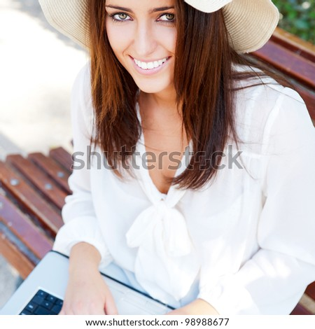 Young elegant woman wearing straw hat and white dress with laptop sitting on bench at park and looking away - stock photo