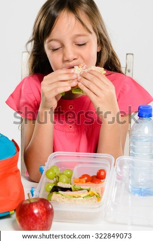 Young elementary school girl eating enjoying her healthy sandwich from her lunch box filled with nutritious food - stock photo
