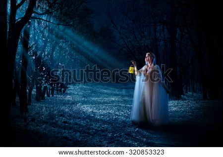 Young elven girl with lantern at night forest - stock photo