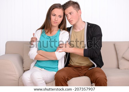 Young emotional couple sitting on sofa at home - stock photo