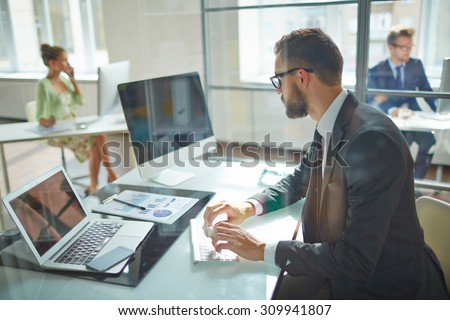 Young employee looking at computer monitor during working day in office - stock photo