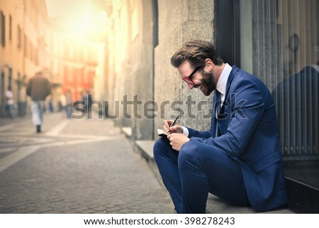 Young employee sitting outdoors - stock photo