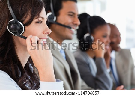 Young employee working with a headset and accompanied by her team - stock photo