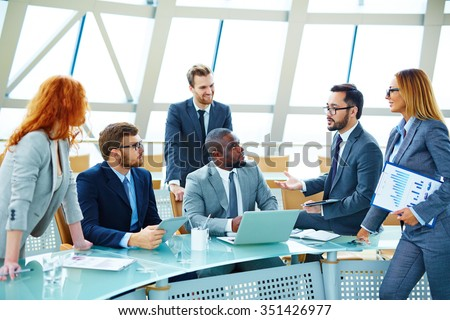 Young employees discussing and explaining new ideas at meeting - stock photo
