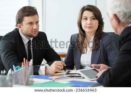 Young employees talking with boss during business appointment - stock photo