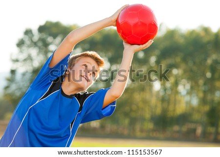Young energetic teen boy jumping to red ball outdoors. - stock photo