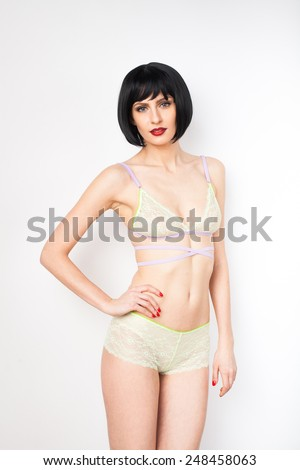 young energetic woman with colorful lingerie smiling relaxed on white background - stock photo