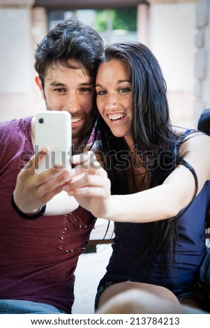 Young engaged couple taking a selfie - stock photo