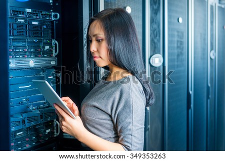 Young engineer businesswoman with tablet in network server room - stock photo