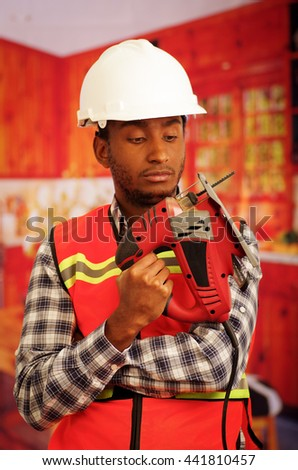 Young engineer carpenter wearing square pattern flanel shirt with red safety vest, holding jigsaw smiling to camera - stock photo