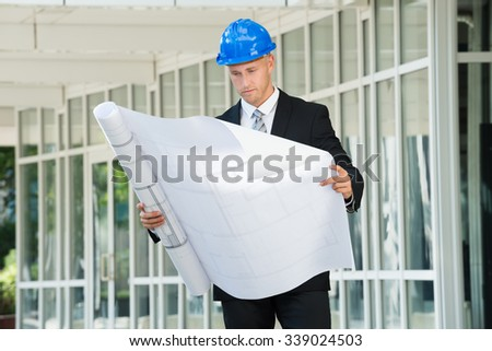 Young Engineer In Helmet Examining Construction Project - stock photo