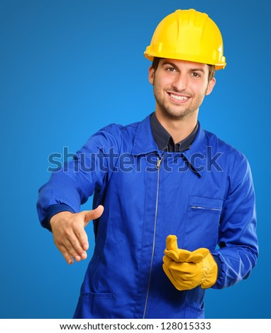 Young Engineer Offering Handshake Isolated On Blue Background - stock photo