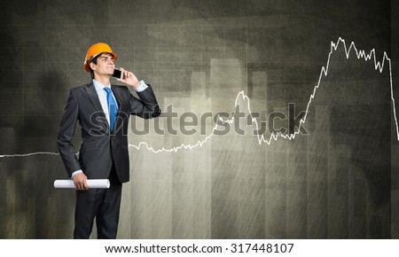 Young engineer wearing helmet talking on mobile phone  - stock photo
