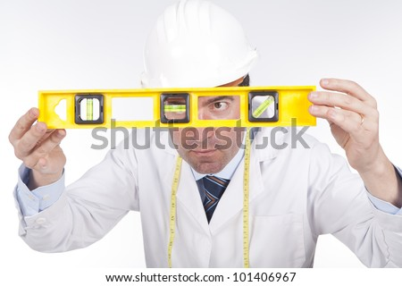 young engineer with a helmet on paying attention and using a level - stock photo