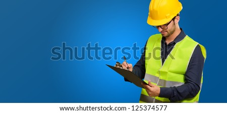Young Engineer Writing On Writing Pad On Blue Background - stock photo