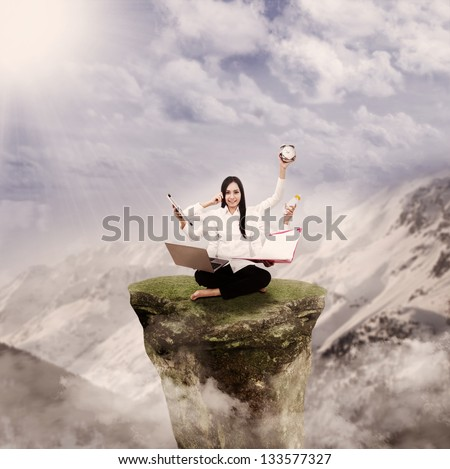 Young entrepreneur is multitasking on top of a mountain rock - stock photo