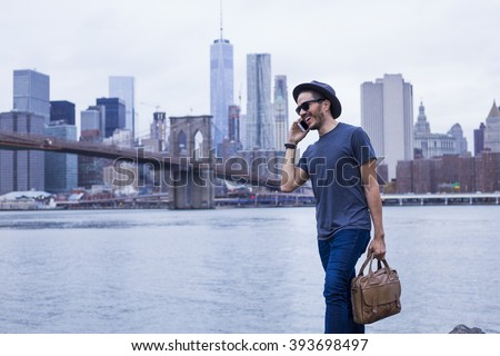 Young entrepreneur making a phone call and carrying a briefcase in New York - stock photo