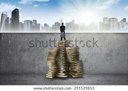 Young entrepreneur standing on a pile of textbooks and look at a town - stock photo