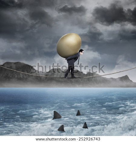 Young entrepreneur walking on the rope above the sea while carrying a golden egg - stock photo