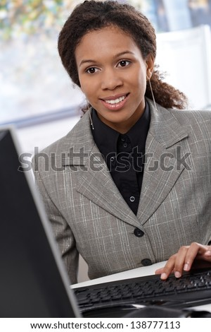 Young ethnic businesswoman sitting at desk, working with computer, smiling. - stock photo