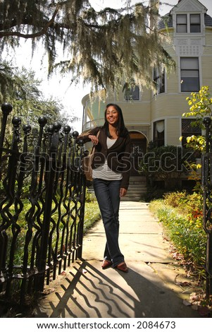 Young ethnic college student in front of home - stock photo