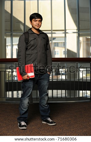 Young Ethnic Student standing holding a copybook with college building as background - stock photo