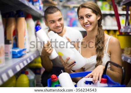 Young european  people choose some detergents in the shop