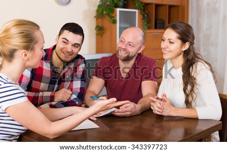 Young european spouses sitting with documents and asking friends for advice - stock photo