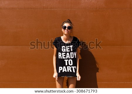 Young European teenage brunette curly model posing near brown ribbed wall, grimacing, jumping, wearing blue jeans mini shorts, sneakers, round sunglasses and black t-shirt, ready to party - stock photo