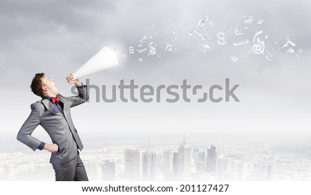 Young excited businessman screaming in paper trumpet - stock photo