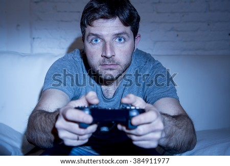 young excited man at home sitting on living room sofa playing video games using remote control joystick with freak intense face expression having fun in gaming addiction - stock photo
