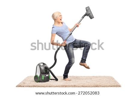 Young excited woman cleaning with a vacuum cleaner and pretending to be playing guitar on the hose isolated on white background - stock photo