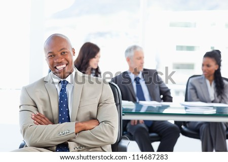 Young executive laughing while crossing his arms and sitting in front of his team - stock photo