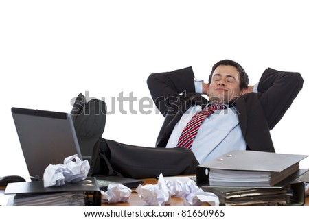 Young executive relaxes with feet at desk. Isolated on white background. - stock photo