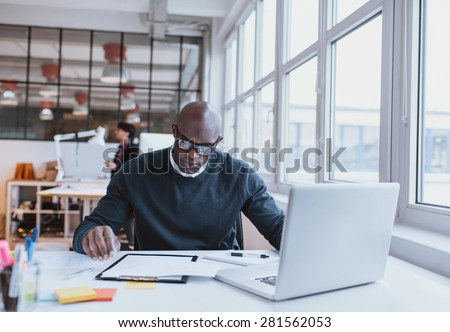 Young executive sitting at his desk with laptop reading a document. African man working in office. - stock photo